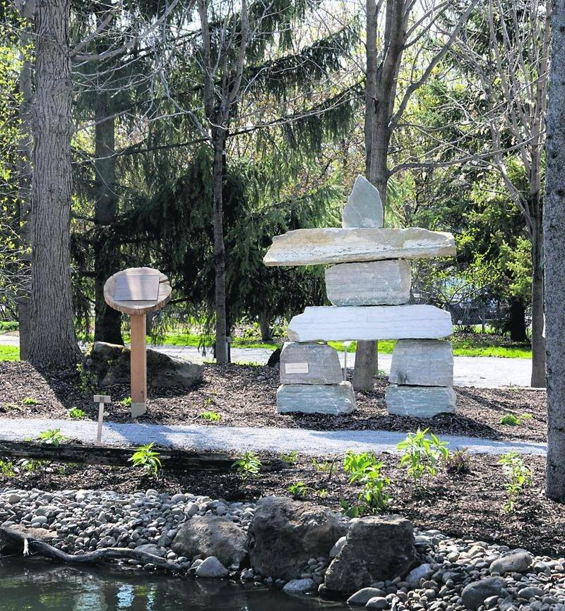 Un imposant inukshuk, un empilement de pierres dont la forme rappelle un humain est installé en bordure d'un sentier de petites roches permettant la visite du jardin. Photo François Larivière | Le Courrier ©