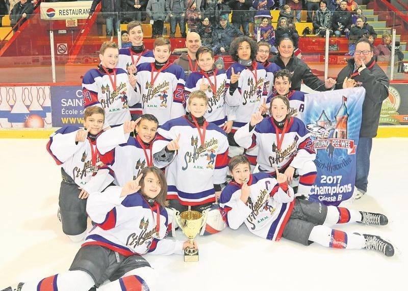 Les joueurs et entraîneurs des Maskas posent fièrement avec le trophée et la bannière de champion.  Photo Robert Gosselin | Le Courrier ©
