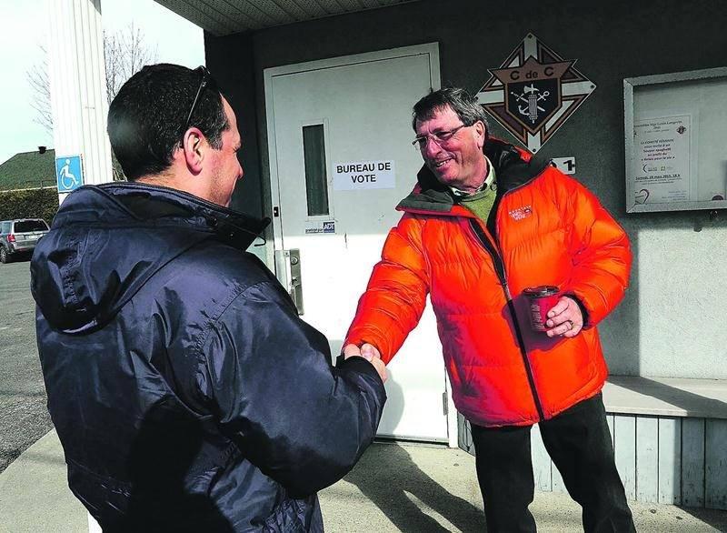 Gilles Carpentier serrait des mains, dimanche, devant le bureau de scrutin à Sainte-Madeleine. Photo Robert Gosselin | Le Courrier ©