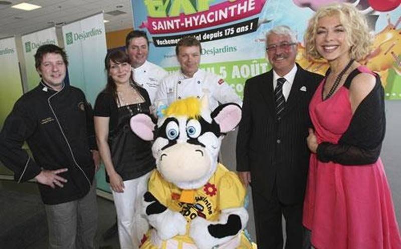 À gauche, les chefs Rock Fortin, Philippe Métayer et Thierry Maurer sont accompagnés de Geneviève Vouligny de Télé-Québec. À droite, le président d'honneur de l'Expo, Léon Sansoucy et la chanteuse et actrice Joe Bocan. Au centre, Mollie, la nouvelle mascotte de l'Expo.