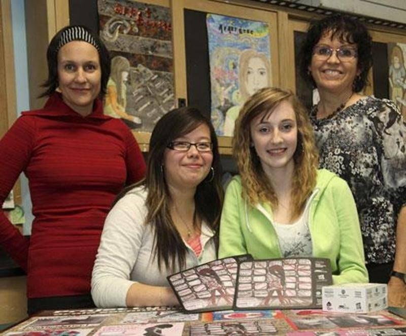 Katherine, Andréa et leurs enseignantes Kim-Renée Richard et Sylvie Racine présentent les ébauches de tapis de souris réalisés dans le cadre d'un projet pour lutter contre la cyberintimidation.