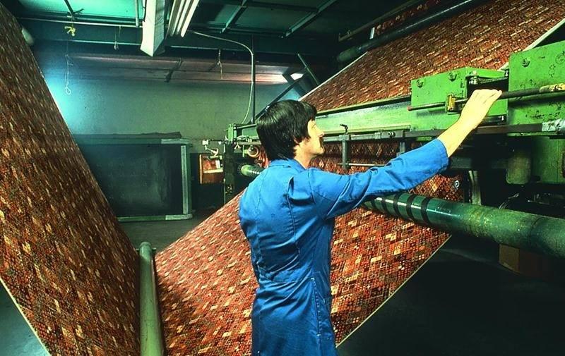 Ouvrier affecté à la surveillance d'une machine à touffeter. Photo : Société d'histoire de la région d'Acton