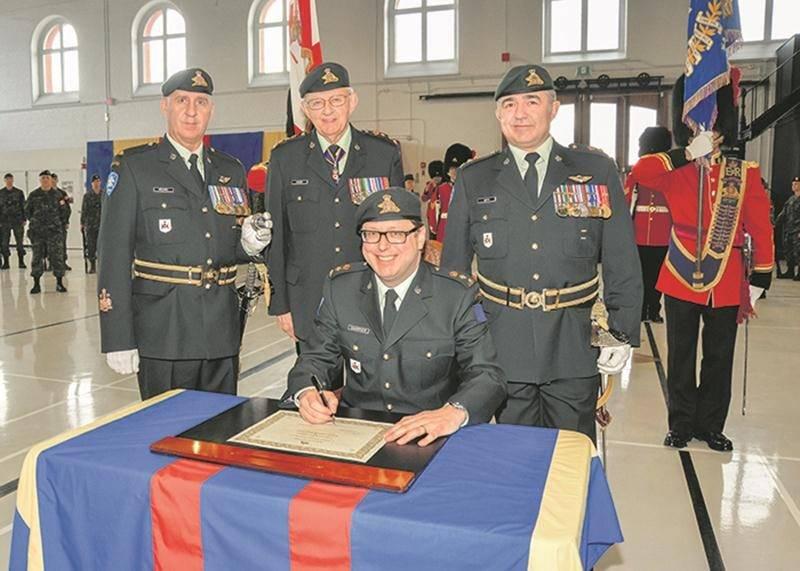 Benoit Chartier signe le parchemin officialisant son titre de lieutenant-colonel honoraire du 6e Bataillon Royal 22e Régiment. Derrière M. Chartier, de gauche à droite, l'adjudant-chef Robyn Bédard (sergent-major régimentaire du 6e Bataillon Royal 22e Régiment), le lieutenant-général à la retraite Richard J. Evraire (colonel du Royal 22e Régiment) et le lieutenant-colonel Steve Hétu (commandant du 6e Bataillon Royal 22e Régiment).