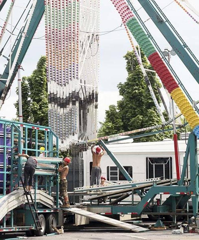 Des travailleurs s'affairent à monter sur le site de l'Expo l'imposant manège que représente la grande roue.