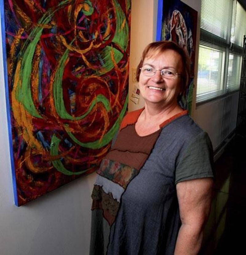 Maryse Laroche Plourde, présidente du conseil d'administration de Visit'art, présentant la toile <em>Jeux-2</em> qu'elle a réalisée à l'aide d'une spatule à cuisine.
