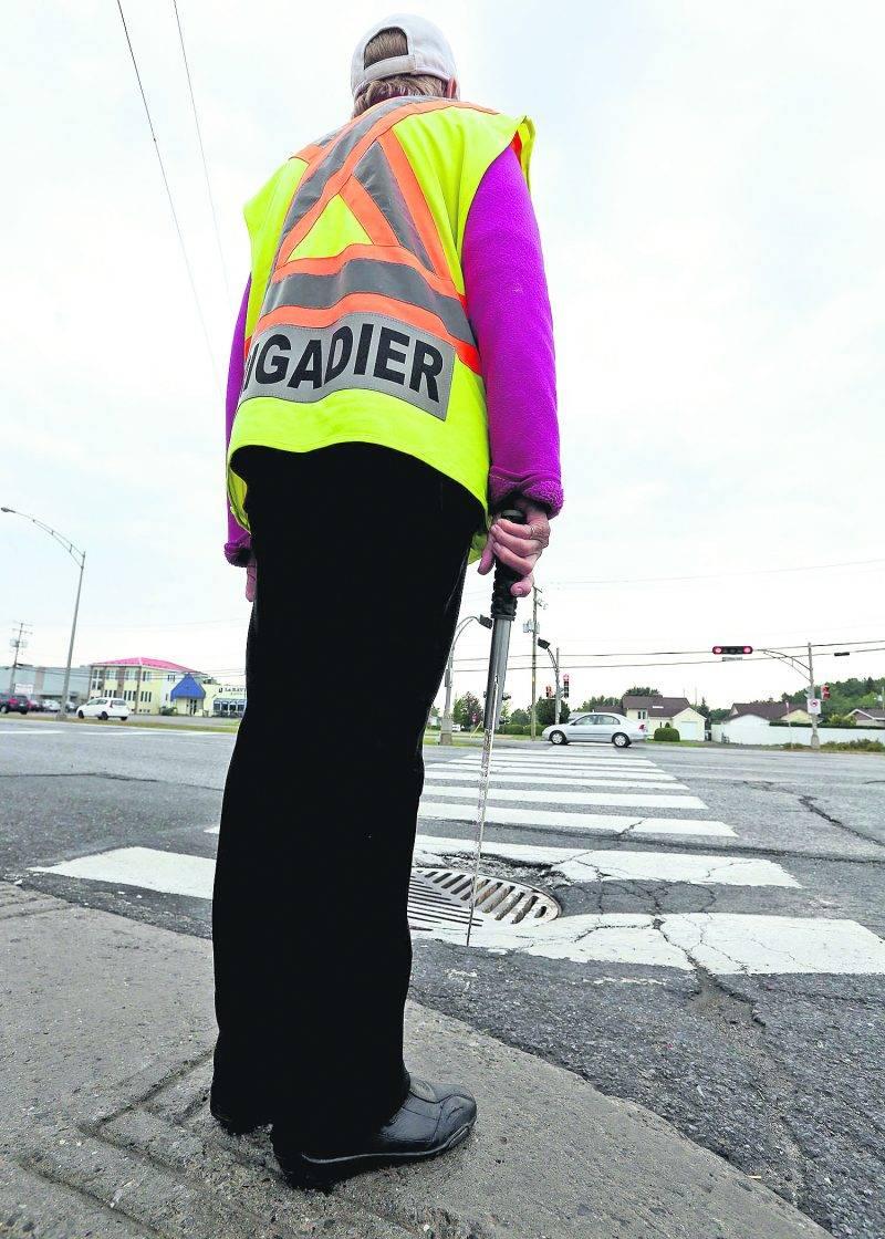 Les nouvelles directives de la Ville de Saint-Hyacinthe concernant la tenue vestimentaire de ses employés indisposent les brigadiers scolaires. Sur la photo, cette brigadière a décidé de se conformer à la politique. Photo Robert Gosselin | Le Courrier ©