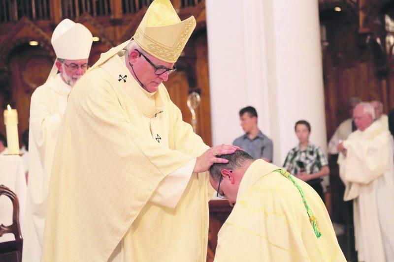 Mgr Luc Cyr, archevêque de Sherbrooke, accomplit le rite de l'imposition des mains à Mgr Rodembourg lors de son ordination. Chacun des nombreux évêques présents a fait le même geste à sa suite pendant la cérémonie. Photo Robert Gosselin | Le Courrier ©