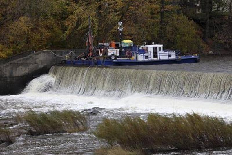 La phase I de travaux de consolidation est en cours au barrage Penman's, au centre-ville de Saint-Hyacinthe. Comme on peut le voir sur la photo, l'entrepreneur général utilise une barge pour procéder aux ancrages qui stabiliseront le déversoir de cet ouvrage en béton datant de 1900. Ces travaux sont réalisés par la compagnie Cimota, de Québec, qui a obtenu en septembre un contrat de 358 863 $ de la Ville de Saint-Hyacinthe. Des contrats totalisant 153 000 $ avaient précédemment été accordés à Te