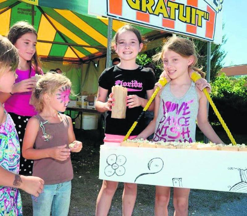 Plusieurs fillettes étaient rassemblées pour partager du maïs soufflé. Environ 18 000 sacs ont été distribués durant le festival.  Photo François Larivière | Le Courrier ©