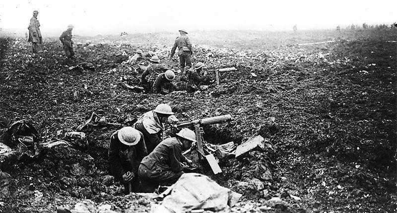 Des artilleurs canadiens se protègent à l'aide de fissures dans le sol causées par des éclats d'obus sur la crête de Vimy en France, avril 1917.  Photo : Bibliothèque et Archives Canada PA-001017