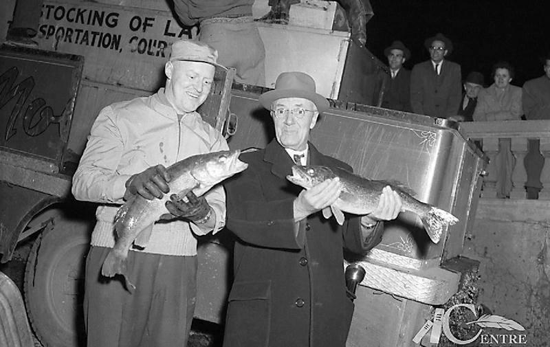 De gauche à droite : Jacques Campbell et Eugène Côté, industriel, respectivement secrétaire adjoint et président de l'ACPY, lors de l'ensemencement de la rivière Yamaska en 1956 en amont du barrage de la Penman's. Centre d'histoire de Saint-Hyacinthe, Fonds Studio Lumière, AP-05491.