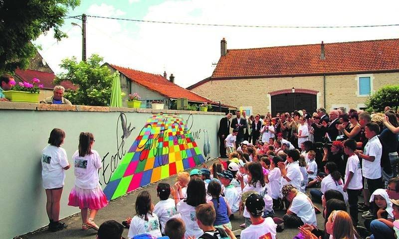Lors de l'inauguration, la foule était rassemblée devant le petit muret peint par l'artiste, situé à l'entrée de l'école.  Ginette Berthiaume