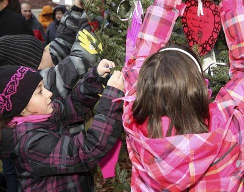 Des élèves de l'école internationale Bois-Joli/Sacré-Coeur ont attaché dans l'Arbre de Paix les décorations qu'ils ont confectionnées et sur lesquelles ils ont inscrit des gestes de paix.