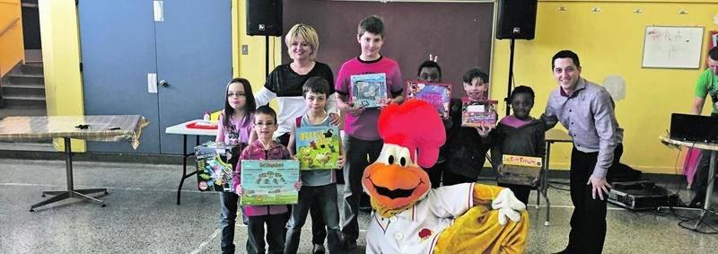 Nancy Greenland, de la Fondation FÉE, et Steve Deslauriers, de la Rôtisserie Saint-Hubert, ainsi que la mascotte Hubert, accompagnent les élèves qui ont remporté des jeux éducatifs.