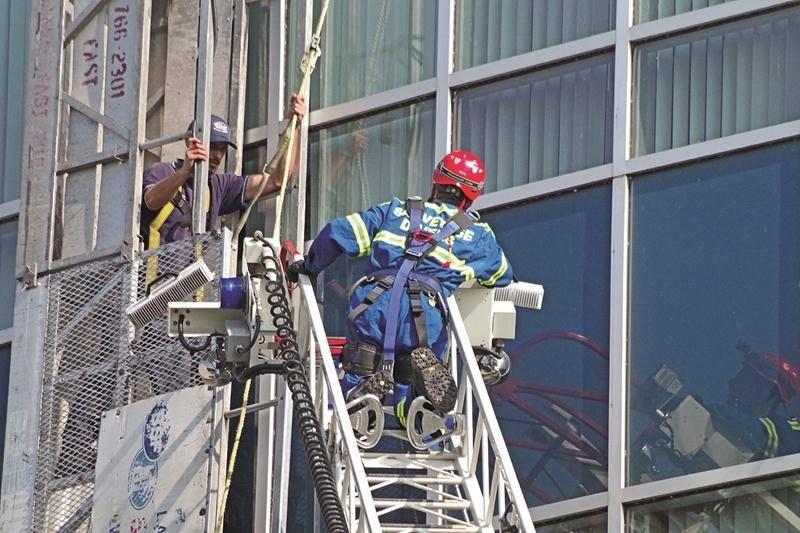 L'un des deux employés prisonniers de la nacelle attend d'être secouru par les pompiers. Photo Dominique St-Pierre