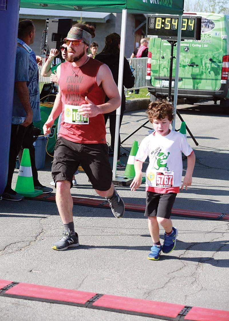 Jeunes et moins jeunes étaient réunis sur le parcours. Ici, on voit un coureur qui termine le 10 km et un petit  bonhomme qui a relevé le défi de 5 km.