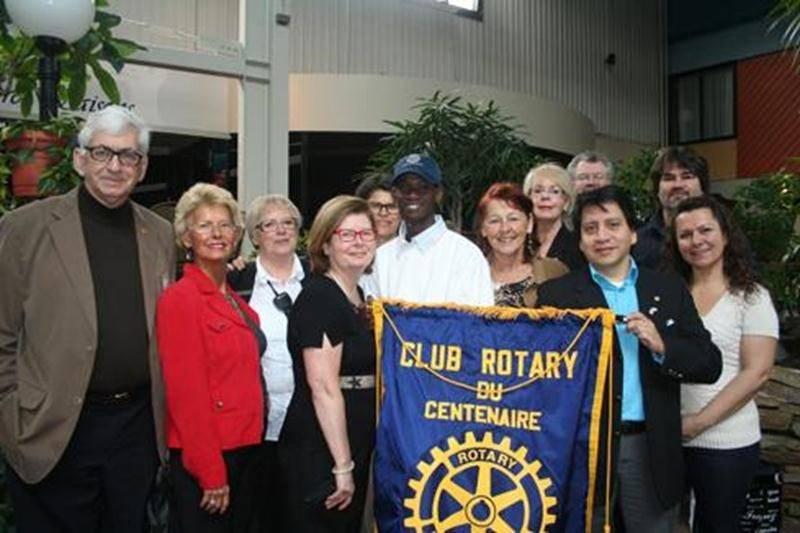 Les membres du Club Rotary de Saint-Hyacinthe encerclent Rodrigue, le fils adoptif de «Maman Nicole» et Nicole Pageau (au centre de la bannière).