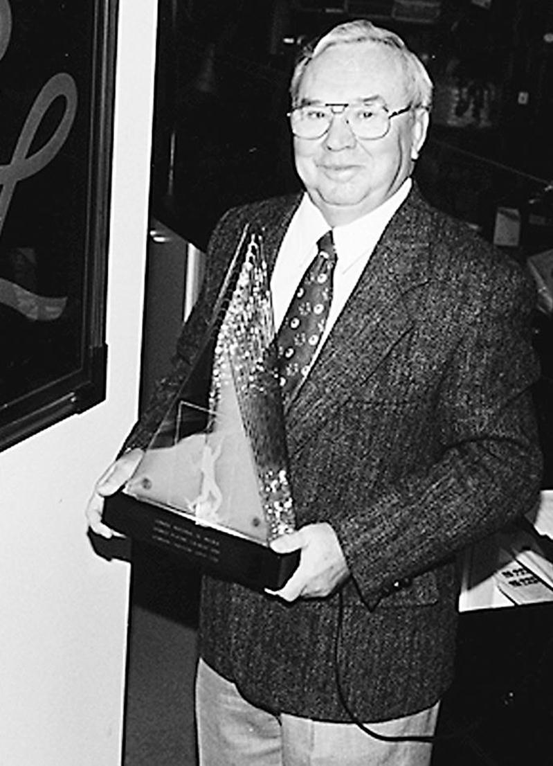 Germain Larivière pose fièrement avec le Trophée Hermès remis par le Conseil national du meuble en 1996.