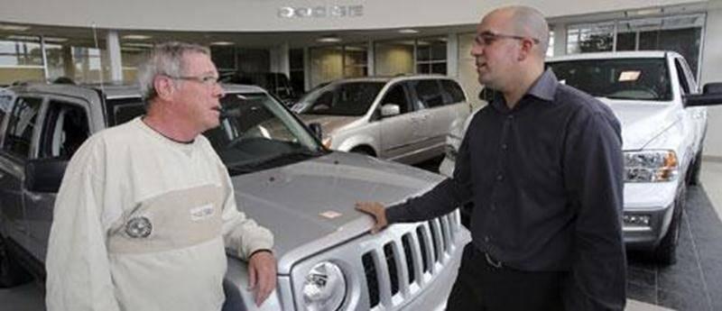 Un représentant de chez Chrysler en compagnie d'un client en ce premier samedi d'ouverture pour le concessionnaire du boulevard Choquette.