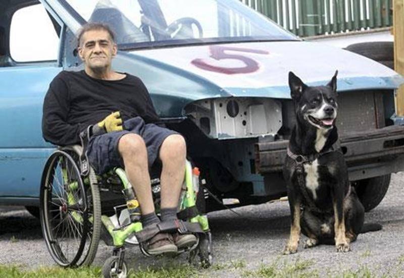 Marc Dumoulin et son fidèle compagnon, Spot, avec à l'arrière-plan le véhicule en préparation afin qu'il puisse participer au derby de démolition de l'Expo.