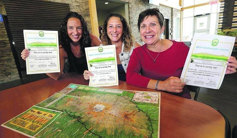 Vicky et Nancy Lachance ainsi que Sylvie Bélair montrant fièrement leurs certificats prouvant qu'elles ont monté complètement le mont Kilimandjaro. Photo Robert Gosselin | Le Courrier ©