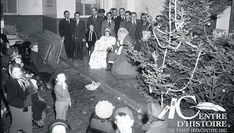 Le père Noël à l'Académie Girouard le 24 décembre 1950 lors du dépouillement de l'arbre de Noël pour les enfants pauvres de Saint-Hyacinthe. Studio Lumière, coll. Centre d'histoire de Saint-Hyacinthe, Fonds CH116.