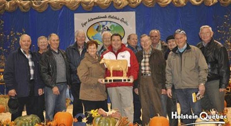 Au centre de la photo, Martin Léonard tient le trophée portant le nom de son père. Il est entouré d'Hermel Giard, de son épouse Huguette Perrault, de leur fils Simon et des anciens récipiendaires de la reconnaissance.