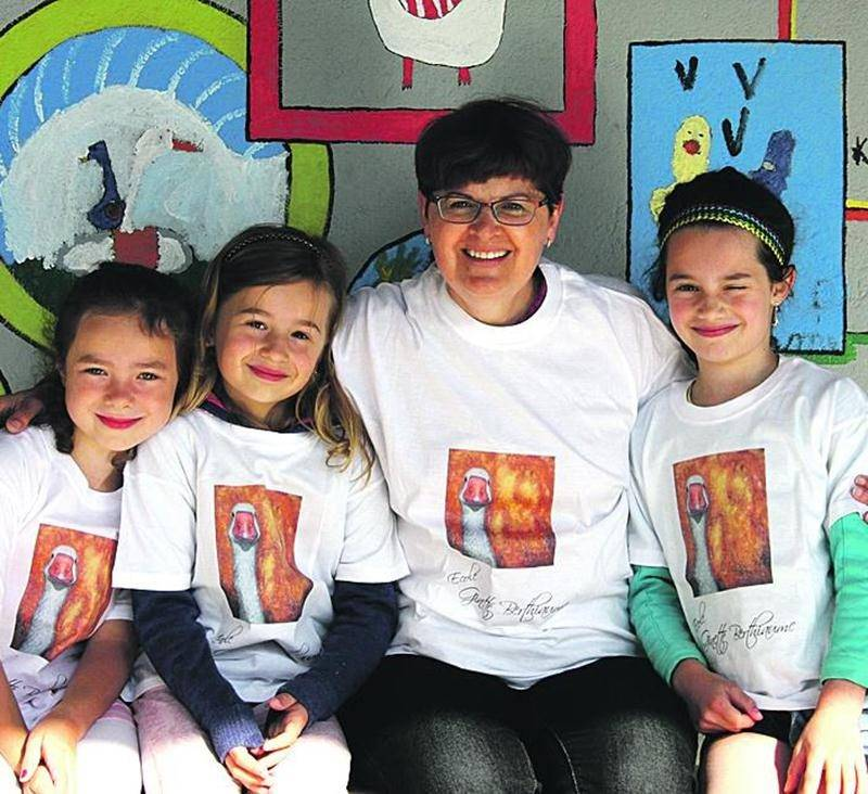 Ginette Berthiaume en compagnie de quelques enfants devant la mosaïque peinte par les élèves de l'école. Ginette Berthiaume