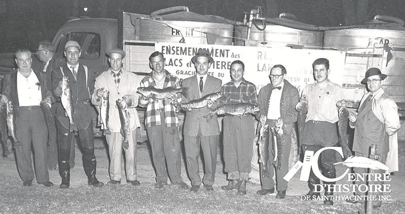 Léo-Paul Robert, président du Club Maska, est sixième en partant de la gauche. À l'arrière, le camion-citerne ayant servi au transport des poissons dans la nuit du 23 au 24 avril 1957.   Centre d'histoire de Saint-Hyacinthe, CH116.