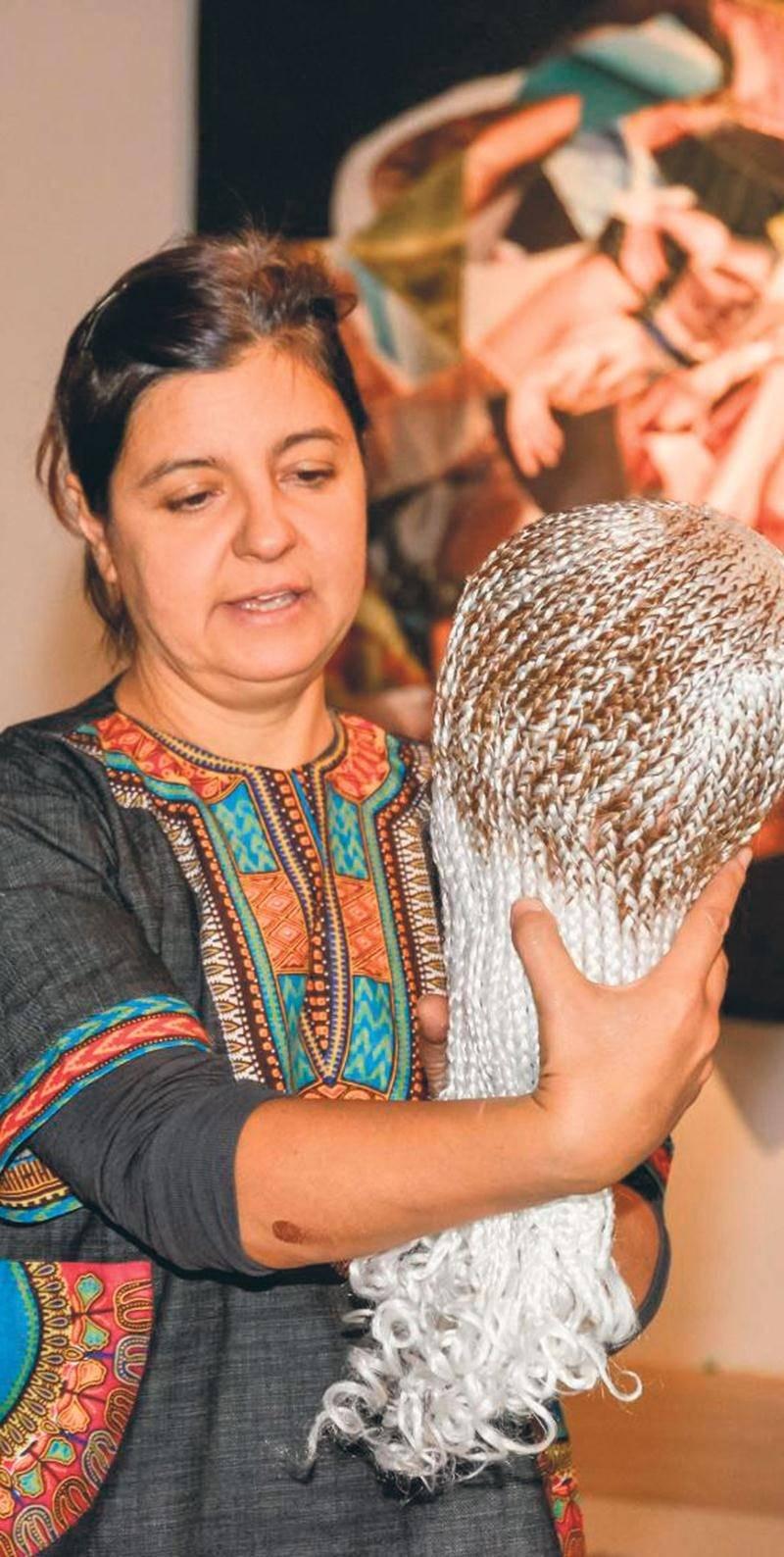 L'artiste Giorgia Volpe tenant l'une des « têtes d'Aissatou », une œuvre consistant en des têtes de coiffure en plastique recouvertes de tresses de cheveux synthétiques. Photo François Larivière | Le Courrier ©