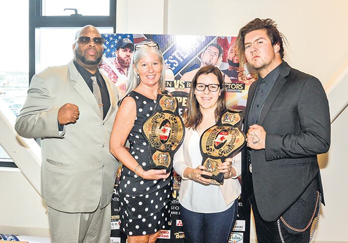 Sur la photo, les champions par équipe NWA, Dru Onyx (à gauche) et le Maskoutain Mike Marston (à droite), entourent Guylaine Blain, coprésidente d'honneur pour le Défi têtes rasées et organisatrice du gala, et Coralie Nault, chargée de projet à Leucan Montérégie.