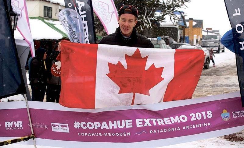 Julien Pinsonneault posant fièrement avec le drapeau canadien au fil d'arrivée de la Copahue Extremo, épreuve de course en raquettes disputée en Argentine, où il a raflé la 1re place au 10 km. Photo courtoisie Copahue Extremo