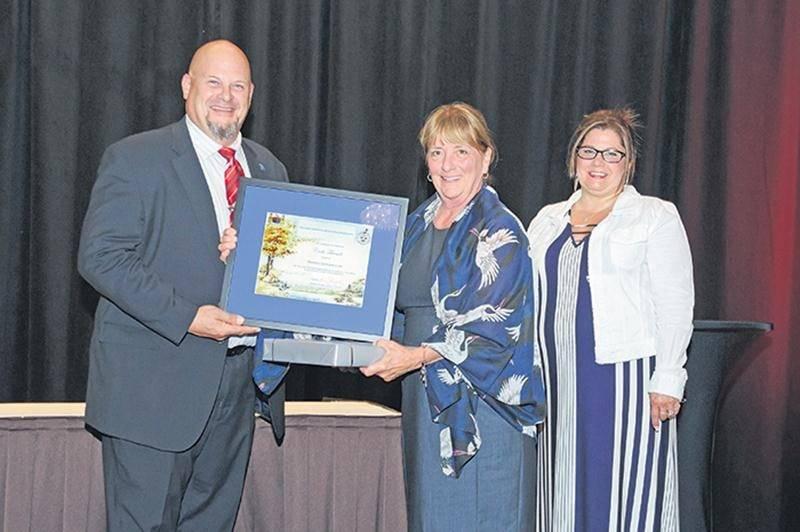 Cécile Tétreault est entourée de Jonathan Nyborg, président de l'Association canadienne des producteurs de semences, et de la conjointe de celui-ci, Denise Nyborg, lors de la remise de son prix en juillet. Photo courtoisie