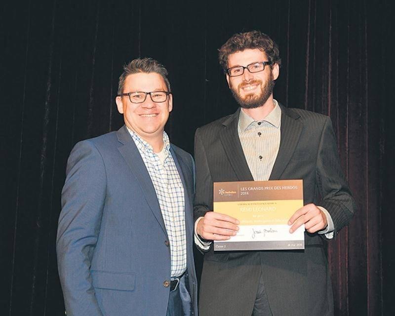 Le journaliste Rémi Léonard recevant son prix des mains de Benoit Caron, vice-président des opérations, TC Média.