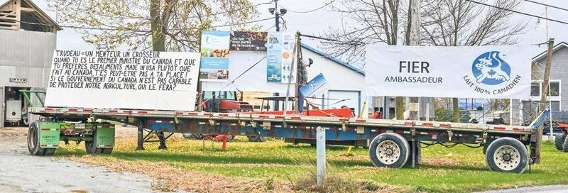 Une large remorque sert de support à plusieurs affiches installées devant une ferme laitière de la rue des Seigneurs Est. Ces affiches dénoncent la politique du gouvernement Trudeau concernant le nouvel accord de libre-échange. Photo François Larivière | Le Courrier ©