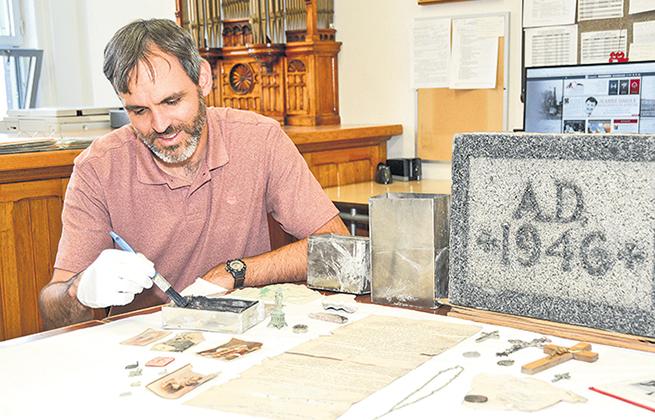 David Bousquet devant une partie du contenu de la boîte en question. On remarque notamment sur la table le certificat de bénédiction et la pierre angulaire qui porte l'année de la construction.