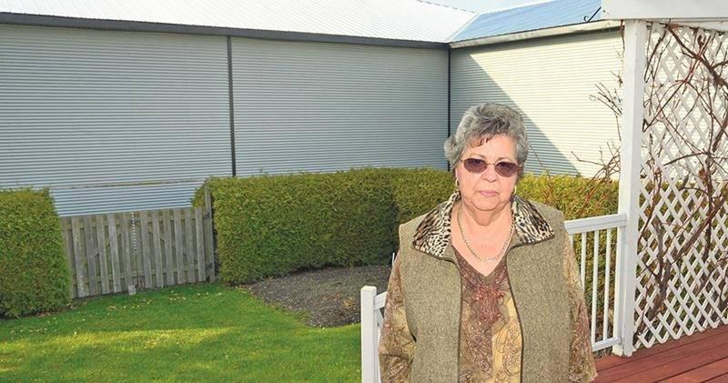 Noëlla Paquette dans sa cour arrière de la rue Demers à l'automne 2014. Derrière sa haie, le garage qui lui empoisonne l'existence depuis ce temps. Photothèque Le Courrier ©
