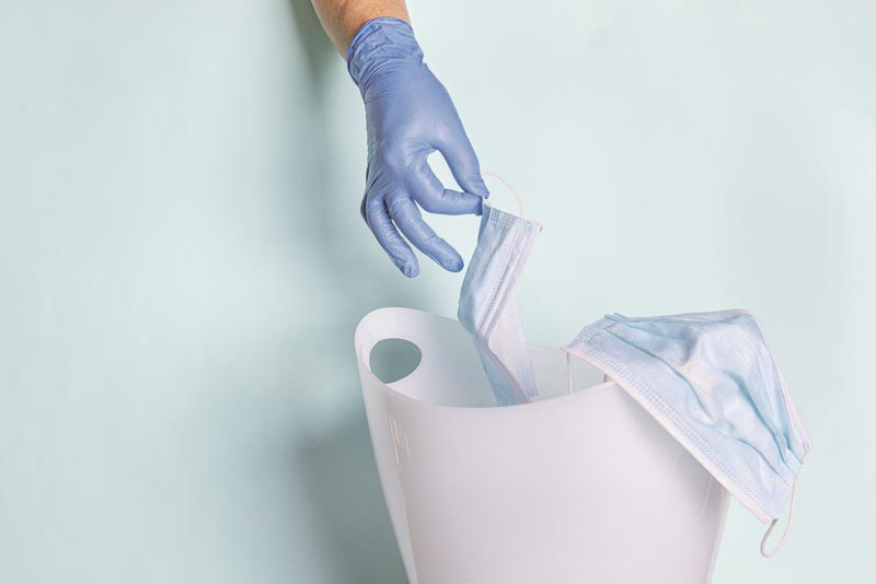 Female hand in disposable rubber gloves throws face mask into trash can. Coronavirus outbreak, quarantine concept. Protect covid-19 during global pandemic