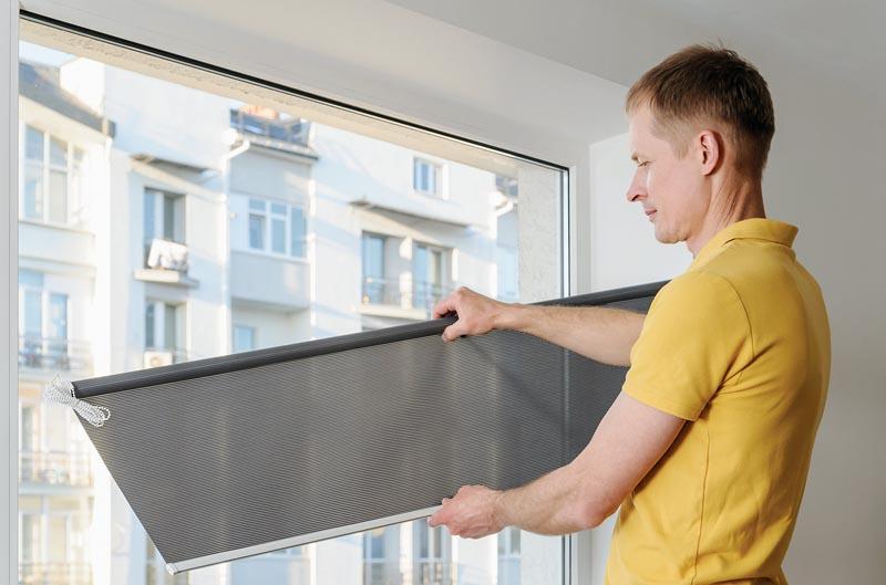 Man is holding fabric window blind gray.